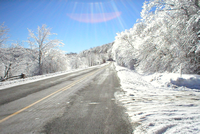 Paved road in winter, with snow on the ground and in the trees on both sides of the road.