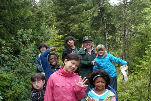 Woman in Forest Service uniform posing with seven young boys and girls.
