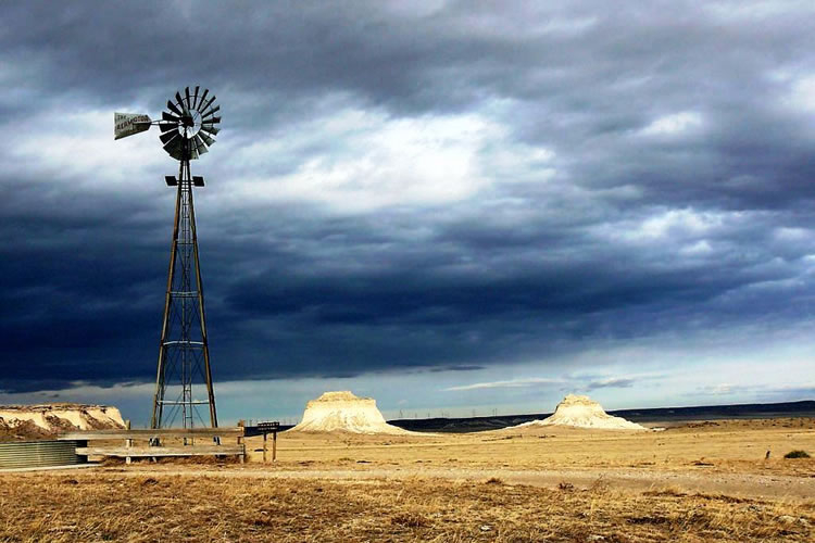A windmill and stock tank, with the Pawnee Buttes in the background on the Pawnee National Grassland.