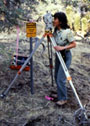 A Forest Service employee looking through a surveying instrument mounted on a tripod.
