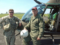 two men in flight suits one holding a flight helmet stand in front of