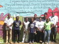 Students and teachers from Overbrook Environmental Center stand in front of a colorful mural.