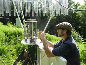 Nicholas Grant, a hydrologist with the U.S. Forest Service, is pictured programming a NOAH IV Total Precipitation Gauge to collect and store total precipitation data every 15 minutes. Photo by Iam Halm, U.S. Forest Service.