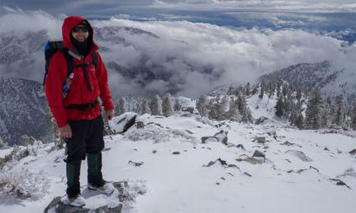 A photo of Jeoy Chong standing high on a snowy mountain.