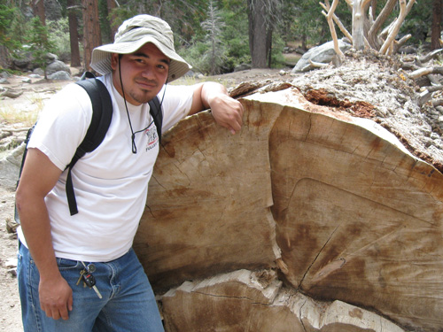 A photo of Jose Sanchez standing next to a downed tree.