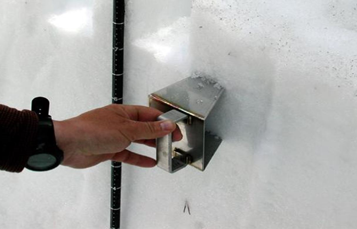 A close up of a metal tool used to remove a sample of snow.