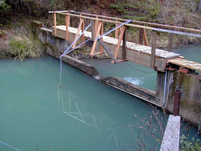 A bridge-mounted boom suspends a turbidity probe in a pond.