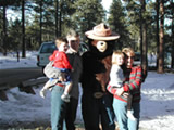 Photo of Smokey with a family at Christmas Tree cutting area