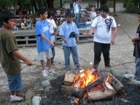 [Photograph]: Students roasting marshmellows around a campfire ring.