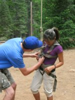 [Photograph]: Instructor attaching harness on student for team building activity.
