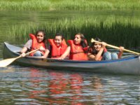 [Photograph]: Four girls in a canoe.