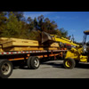 Unloading trail timbers from a truck with a backhoe.