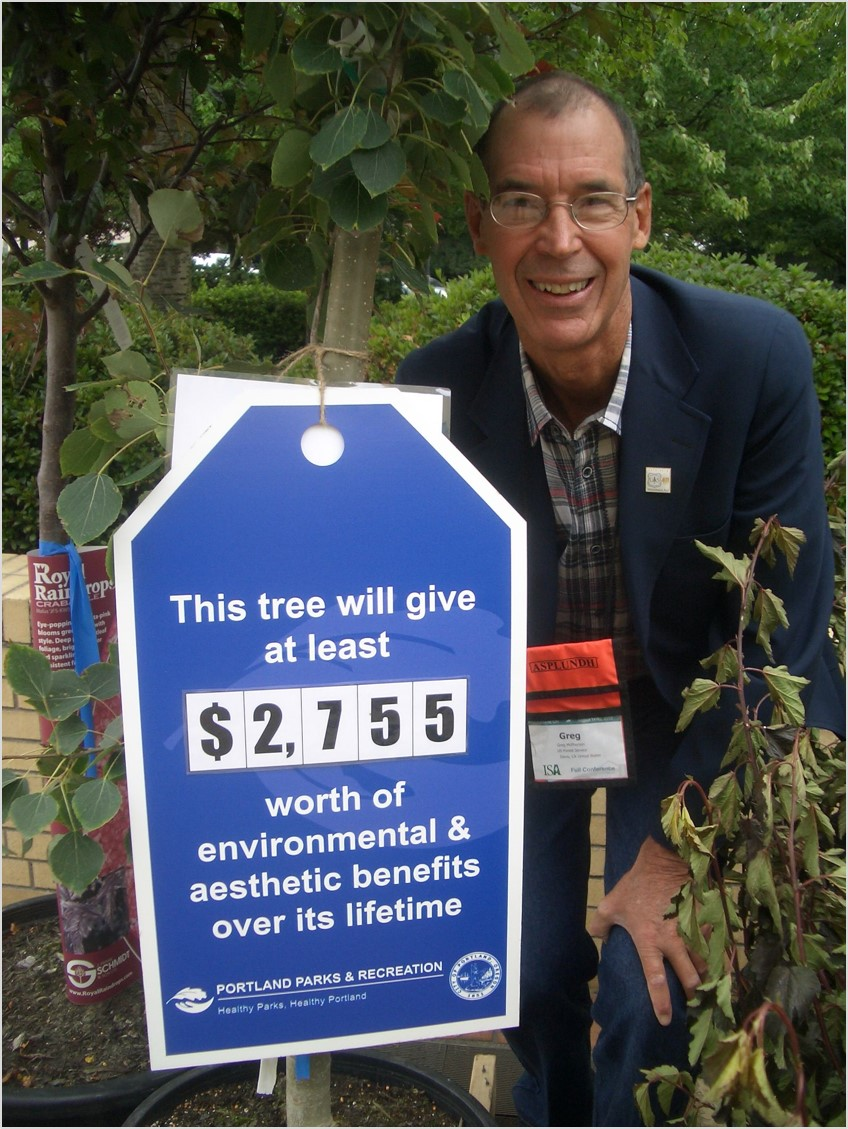 Greg McPherson standing with a tree and its environmental benefit price tag