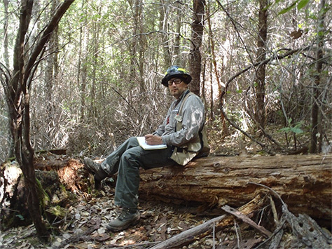 Frank Lake sitting on a log at a research site.