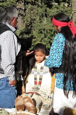 A young maiden being blessed by medicine man.