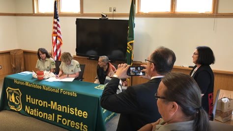 Regional Forester Kathleen Atkinson signs the MOU while Tribal representatives watch.