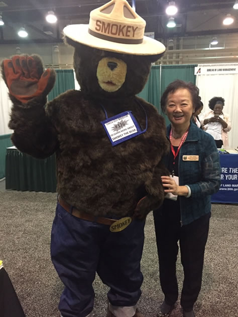 Vina Yang stands with Smokey Bear.