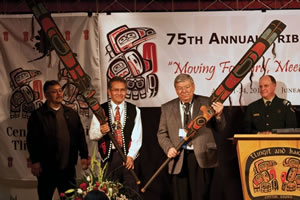 Central Council President Emeritus Ed Thomas holds the Raven staff and President Bill Martin holds the Eagle staff as Deputy Regional Forester Paul Brewster and Tribal Liaison Donald Frank look on.