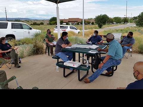 Representatives from the Santa Fe National Forest and the Pueblo of Jemez having a discussion at a picnic table under a shelter at the Santa Fe National Forest Supervisor's Office.