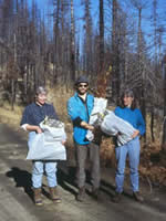 man and two women holding bags of seedlings.