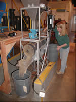 woman working with a seed cleaning equipment.