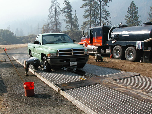 man washing the underside of a Forest Service truck with a power sprayer.
