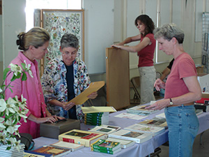 four women preparing publications and displays for a wildflower show.
