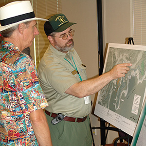 uniformed Forest Service representative discussing a recreation project with a citizen.
