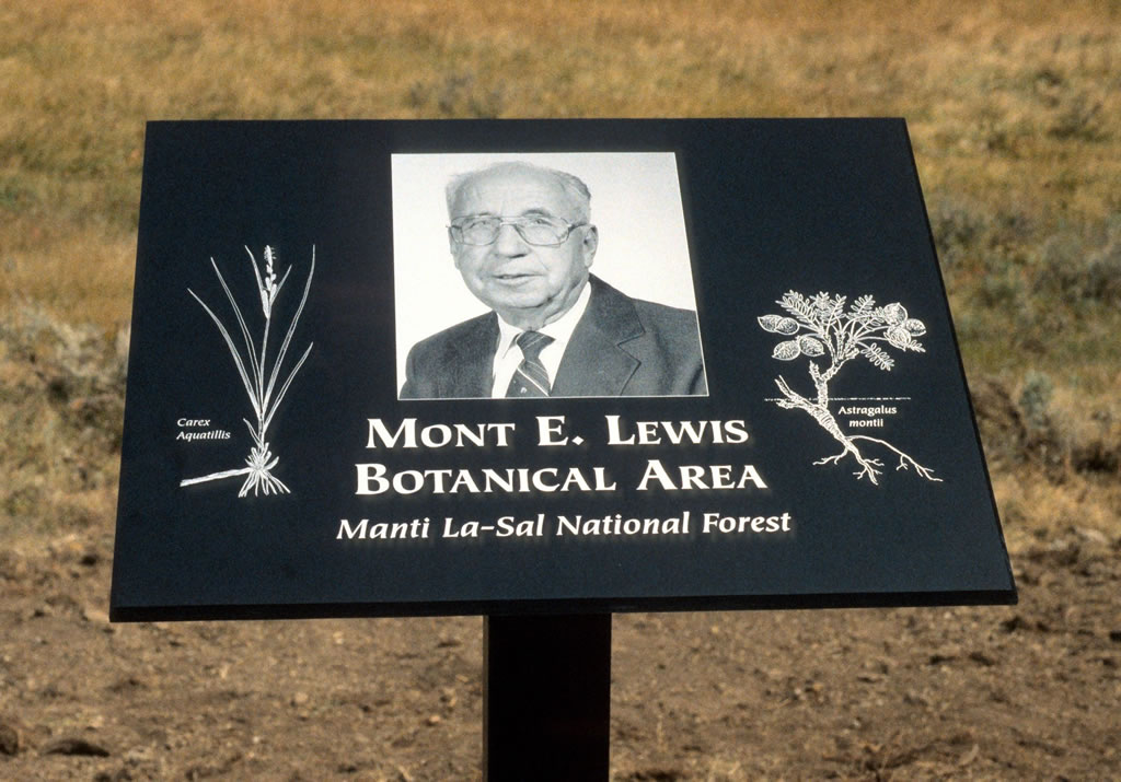 Mont E. Lewis Botanical Area sign on the Manti La-Sal National Forest with Mont Lewis's picture on it.