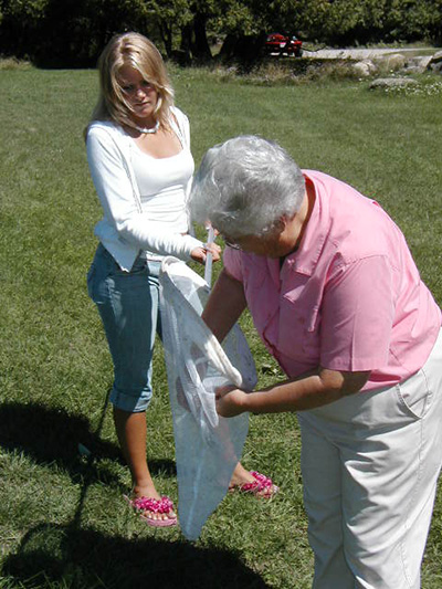 Picture of two women, one holding a capture net, the other reaching into the net to tag a monarch butterfly.