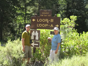 A man and a woman standing by a trail sign.