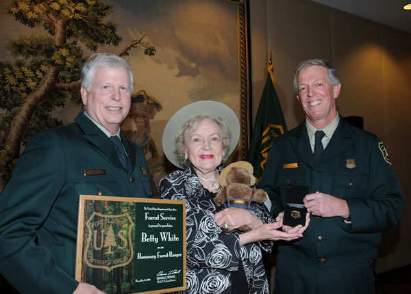 A picture of honorary forest ranger Betty White, Forest Service Chief Tom Tidwell, and Forest Service Associate Chief Hank Kashdan.  Chief Tidwell is holding a plaque for Betty White and Betty White is hugging a small, stuffed Smokey bear.
